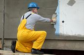 stock photo of trowel  - Worker spreading mortar over styrofoam insulation and mesh with trowel - JPG