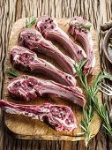 pic of lamb chops  - Raw lamb chops with garlic and herbs on the old wooden table - JPG