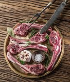 picture of lamb chops  - Raw lamb chops with garlic and herbs on the old wooden table - JPG