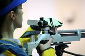 stock photo of rifle  - beautiful young woman aiming a pneumatic air rifle  - JPG