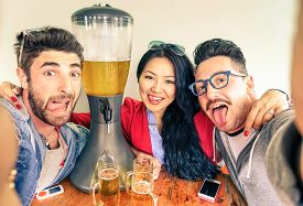 pic of tongue  - Happy friends taking selfie with funny tongue out near beer tower dispenser  - JPG