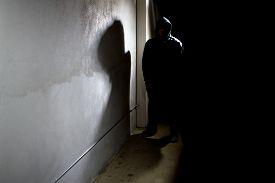 stock photo of hooligan  - hooded criminal stalking in the shadows of a dark street alley - JPG
