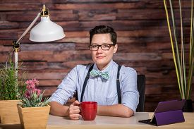 picture of suspenders  - Strict boyish woman in suspenders at desk with a red coffee cup - JPG