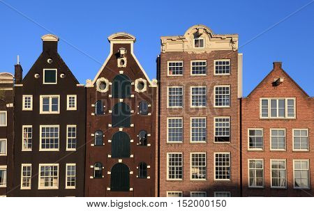 Traditional facade of brick dutch medieval buildings in Amsterdam, Netherlands. Sunset light.