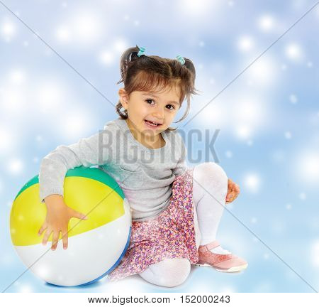 Cute little dark-haired girl with short pigtails on the head, hugging his big , inflatable, striped, vinyl ball.Blue Christmas festive background with white snowflakes.