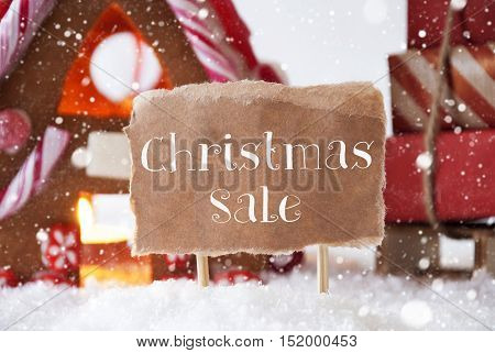 Gingerbread House In Snowy Scenery As Christmas Decoration. Sleigh With Christmas Gifts Or Presents And Snowflakes. Label With English Text Christmas Sale