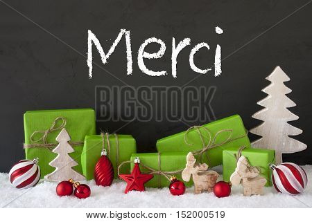 French Text Merci Means Thank You. Green Gifts Or Presents With Christmas Decoration Like Tree, Moose Or Red Christmas Tree Ball. Black Cement Wall As Background With Snow.