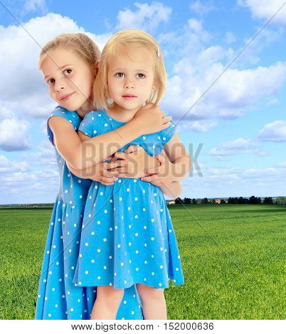 Two charming little girls, sisters , in identical blue dresses with polka dots , cuddling.On the background of green grass and blue sky with clouds. The concept of a family holiday.