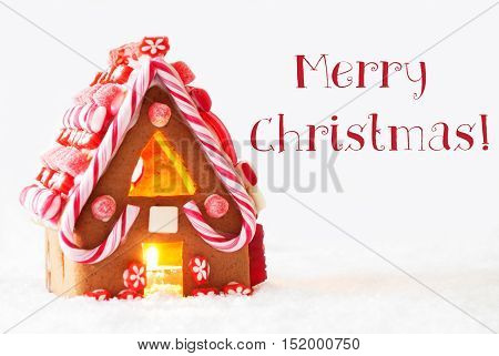 Gingerbread House In Snowy Scenery As Christmas Decoration With White Background. Candlelight For Romantic Atmosphere. English Text Merry Christmas