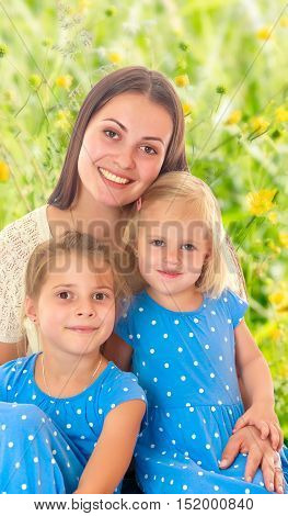 Beautiful young mother with her two daughters. Girls in the same dress with polka dots. Look directly at the camera.The concept of family happiness and mutual understanding between parents.
