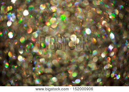 Blurred background of shimmering gems, like a rainbow. Festive backdrop for holiday announcement.