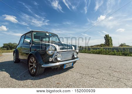 IVREA, ITALY - AUGUST 25, 2015: A classic Mini Cooper parked on a road with a beautiful sky on the background.