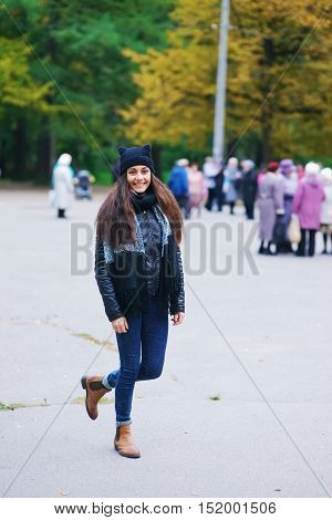 Happy brown-eyed long-haired brunette girl walking in the autumn Park at the weekend, on blurred background urban vacationers