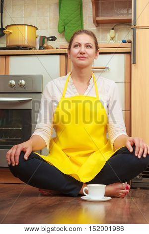 Mature Woman With Cup Of Coffee In Kitchen.