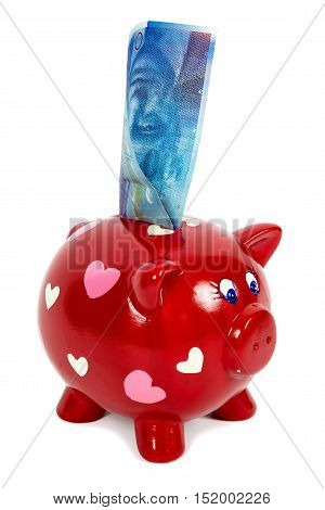Red piggy bank with hearts and 100 swiss franc banknote isolated on white background with clipping path