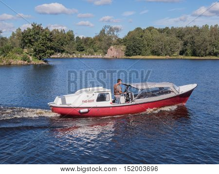 Vyborg, Russia - September 08, 2016: Man controls the motor boat floats on the lake