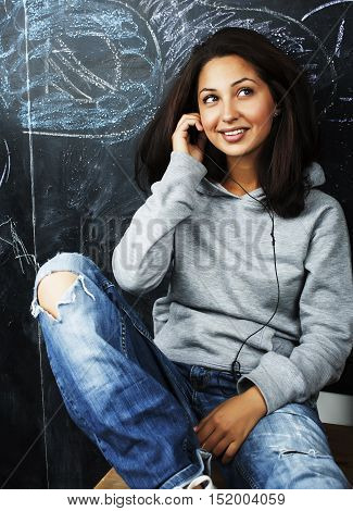 young cute teenage girl in classroom at blackboard seating on table smiling, lifestyle people concept close up