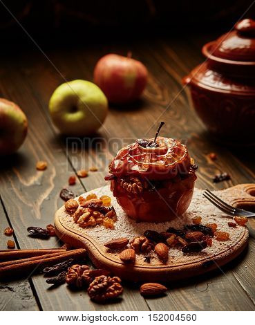 Baked apple with nuts raisins and honey. Wooden background. Healthy lifestyle.Diet and weight loss concept. Low calories dinner. Vitamin B. Healthy food.