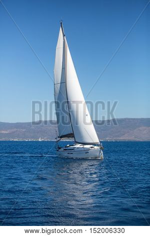 Yacht with white sails in the sea. Luxury boats.