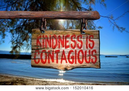 Kindness is contagious motivational phrase sign on old wood with blurred background