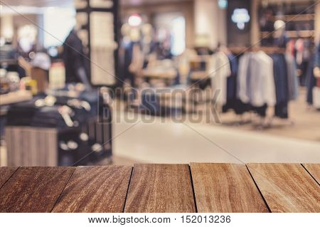 Wooden table top with abstract blurred background of Department store in Shopping Mall