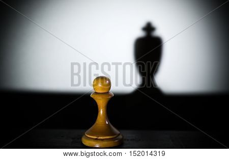 a chess pawn casting a king piece shadow in dark concept of strength and aspirations