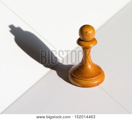 a chess pawn casting a king piece shadow concept of strength and aspirations
