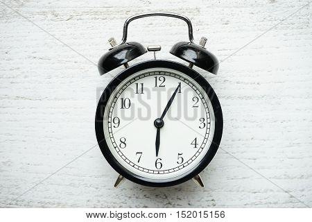 Retro alarm clock on white wooden table