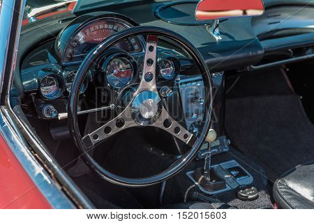 Inside view of a classic american sports car with black interior and red exterior. Closeup of the steering wheel and dash.