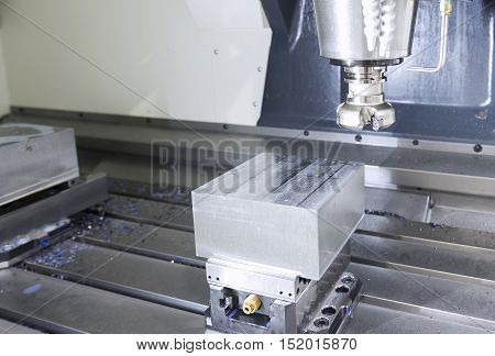 The face milling tool with the raw material work piece on the CNC milling machine.The spindle with holder and tooling for face milling on CNC milling machine