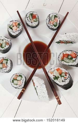 sushi maki rolls salmon with soy sauce and sticks on deep white plate on wooden table
