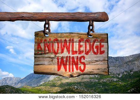 Knowledge wins motivational phrase sign on old wood with blurred background