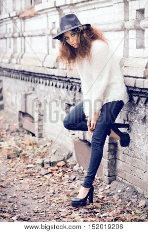 Beautiful girl on brick wall background. Girl in the hat. Gloomy makeup. Halloween. Fashionable woman. Casual wear. Trend clothing. Toned image.