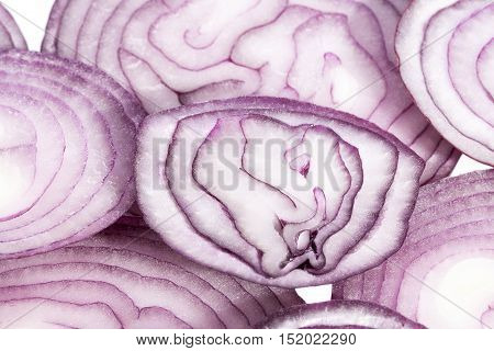 Slices of red onion on white background close up.