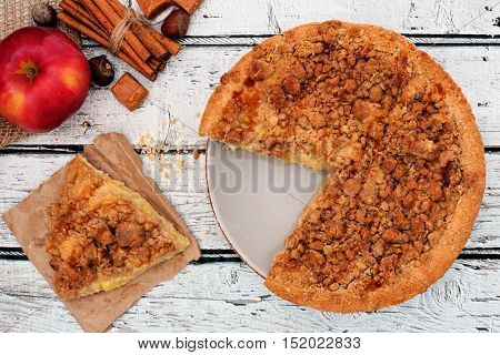 Apple, Caramel Crumb Pie With Slice Removed Over A Rustic White Wood Background
