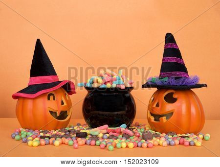 Halloween candy worms spilling from a black cauldron with hard candies and chocolate candy on orange table orange background. Small pumpkin witch jack o lanterns on each side. Copy Space