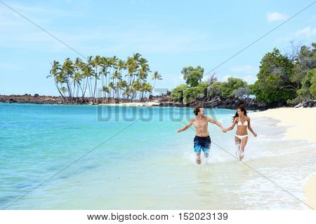 Happy couple laughing together holding hands running having fun splashing water in the ocean waves. Young beautiful fit slim people enjoying their happy lifestyle in paradise destination beach.