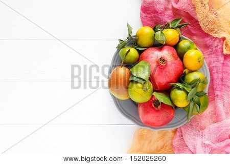 Beautiful set of fruits pomegranate, tangerine, pear on pink textile and white wooden background horizontal image