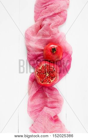 top view of a ripe pomegranate on a pink fabric. Food Fashion minimal style.