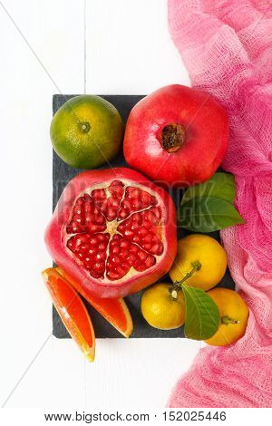 Top view of a set of fruits pomegranate, mandarin, orange on white wooden background. Fruit still life