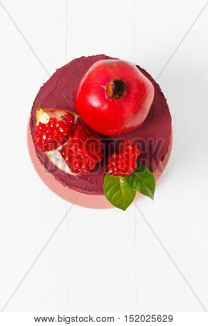Top view of a sweet cake decorated with ripe pomegranate
