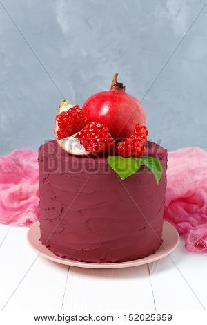 Stylish colors Marsala cake decorated with pomegranate on a gray background. Fruit still life
