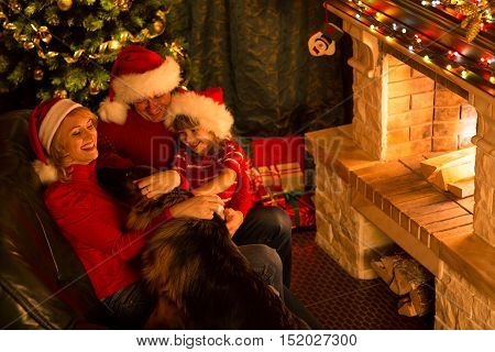 Happy New Year. Family playing with dog in Christmas festive decorated living room. Pet people holiday concept
