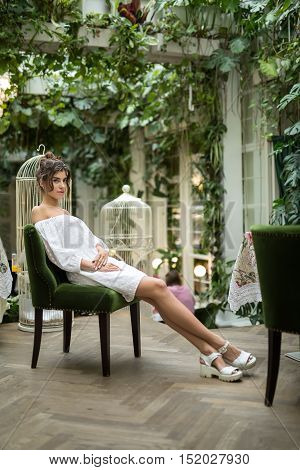 Attractive girl in a white dress and white sandals sits on the green chair in the restaurant with green plants and birdcages. Her legs are crossed, hands are on the thighs. Vertical.