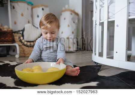 cute happy baby boy eating cookies at home and playing with plate of lemons. Lifestyle indoor capture in cozy modern interior