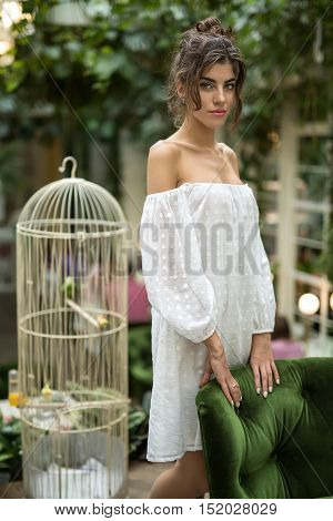 Sexy girl in a white dress stands near the green chair in the restaurant with green plants and birdcage. Her hands are on the chair. She looks into the camera. Vertical.
