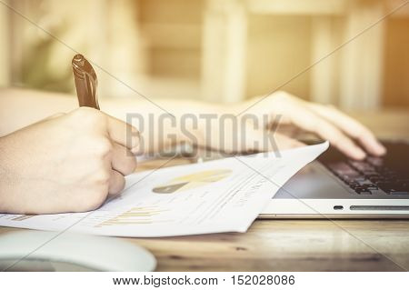 close up Business girl hand holding pen point stock market chart and using laptop on wood desk. vintage effect. selective focus.