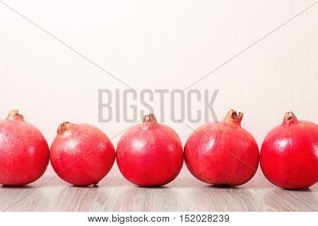 Several ripe pomegranates in a row on the table