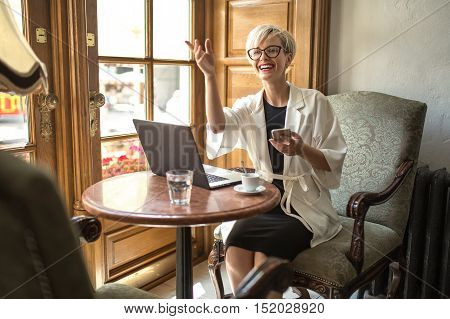 Laughing blonde girl in glasses sits on the armchair at the table with laptop in the cafe and points hand up. She holds the cell in the left hand. Woman wears black dress and a white cloak. Horizontal.