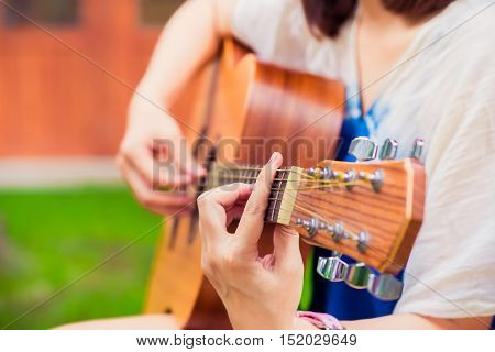 close up Woman playing acoustic guitar. vintage effect. selective focus. release or relax concept.